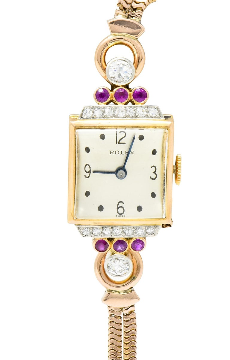 Centering a square watch face and case featuring a domed glass window, blue hands, and dot motif dial markers with numbers at each cardinal point  Flanked by stepped gemstone shoulders featuring a row of bead set diamonds, followed by a row of bezel