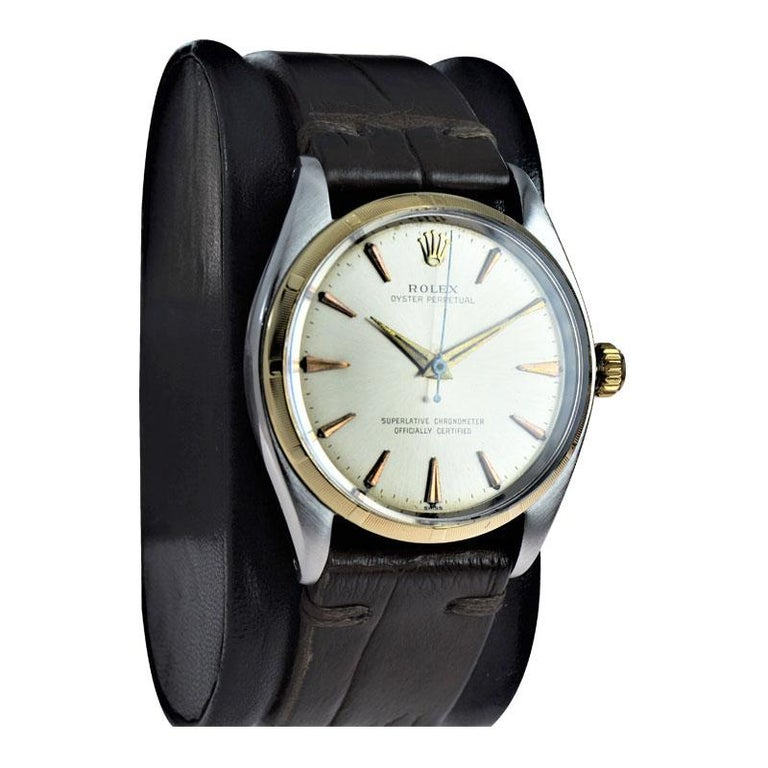 FACTORY / HOUSE: Rolex Watch Co. STYLE / REFERENCE: Oyster Perpetual / Ref. 1003 METAL / MATERIAL: Stainless Steel case / Yellow Gold Bezel CIRCA / YEAR: 1961 DIMENSIONS / SIZE: 40mm x 34mm MOVEMENT / CALIBER: Perpetual Winding / 26 Jewels /