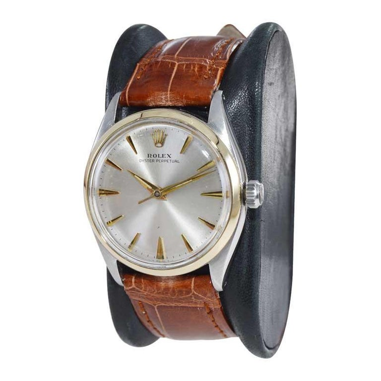 FACTORY / HOUSE: Rolex Watch Company STYLE / REFERENCE: Oyster Perpetual / Reference 6564 METAL / MATERIAL: Steel / 14Kt. Gold Bezel CIRCA / YEAR: Mid 1950's DIMENSIONS / SIZE: 39mm x 34mm MOVEMENT / CALIBER: Manual Winding / 26 Jewels / Caliber
