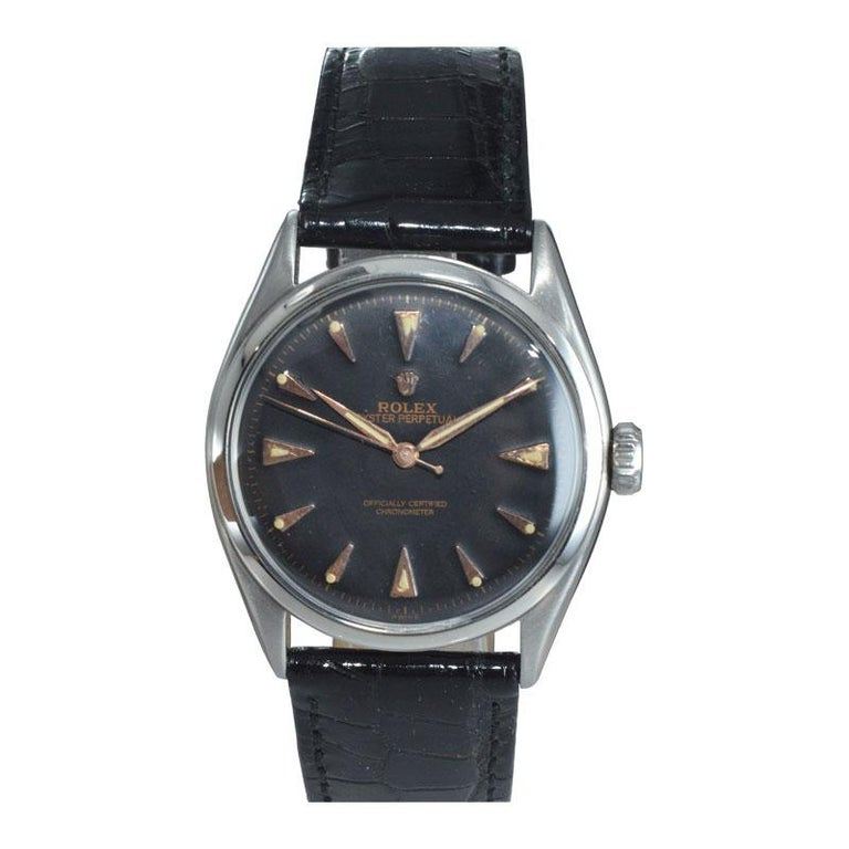 FACTORY / HOUSE: Rolex Watch Company STYLE / REFERENCE: Oyster Perpetual / 6084 METAL / MATERIAL: Stainless Steel  CIRCA / YEAR: 1952 / 1953 DIMENSIONS / SIZE: 39mm X 34mm MOVEMENT / CALIBER: Perpetual Winding / 17 Jewels  DIAL / HANDS: Black with