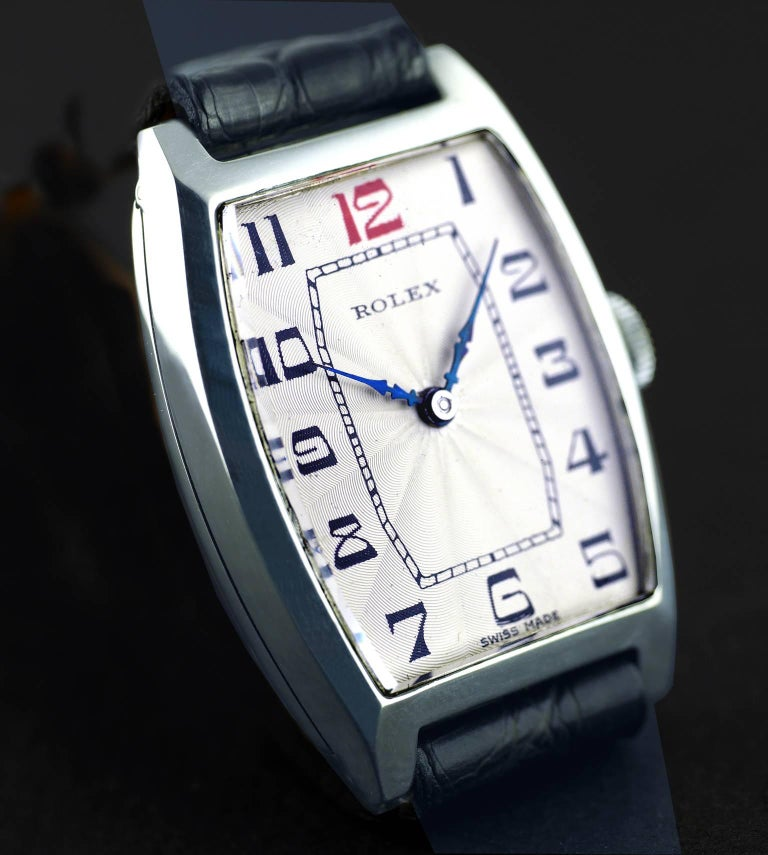 """An Art Deco vintage wristwatch by Rolex made in 1926.  The silver tonneau shaped case marked """"7 World's Records"""" and """"Gold Medal, Geneva - Suisse"""",  hinged silver case hallmarked for Glasgow Import into the United Kingdom in 1926.  15-Jewel movement"""