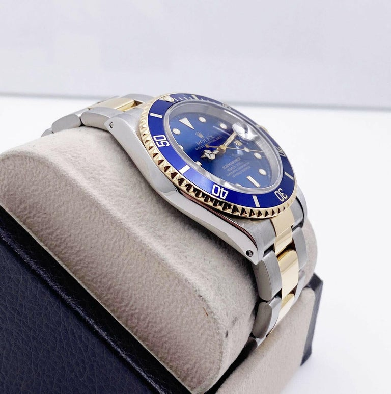Style Number: 16613  Serial: U107***  Model: Submariner  Case Material: Stainless Steel  Band: 18K Yellow Gold & Stainless Steel  Bezel: Blue  Dial: Blue  Face: Sapphire Crystal  Case Size: 40mm  Includes:  -Elegant Watch Box -Certified Appraisal