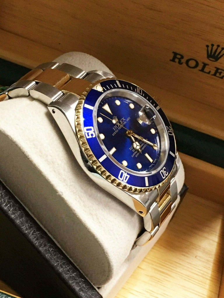 Style Number: 16613  Serial: A912***  Year: 2000  Model: Submariner  Case Material: Stainless Steel  Band: 18K Yellow Gold & Stainless Steel  Bezel:  Blue  Dial: Blue   Face: Sapphire Crystal   Case Size: 40mm  Includes:  -Rolex Box  -Certified