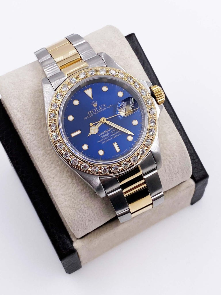Style Number: 16613     Serial: S311***     Model: Submariner     Case Material: Stainless Steel     Band: 18K Yellow Gold & Stainless Steel     Bezel:  Custom Diamond Bezel      Dial: Blue      Face: Sapphire Crystal     Case Size: 40mm