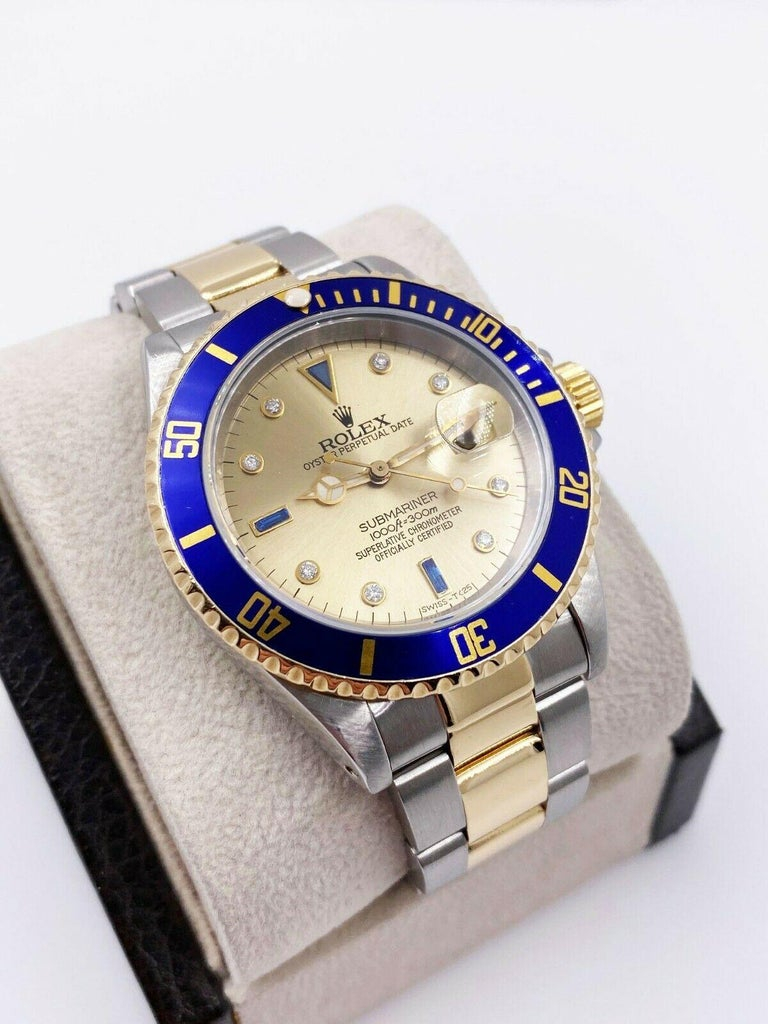 Style Number: 16613     Serial: X566***     Model: Submariner     Case Material: Stainless Steel     Band: 18K Yellow Gold & Stainless Steel     Bezel:  Blue     Dial: Custom Serti Dial     Face: Sapphire Crystal      Case Size: 40mm     Includes:
