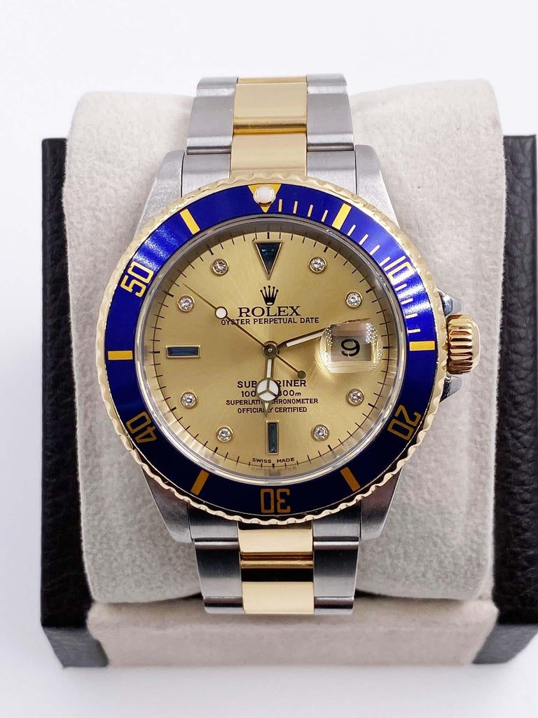 Style Number: 16613  Serial: P680***  Year: 2002  Model: Submariner  Case: Stainless Steel   Band: 18K Yellow Gold & Stainless Steel  Bezel: Blue  Dial: Original Champagne Serti  Face: Sapphire Crystal   Case Size: 40mm   Movement: