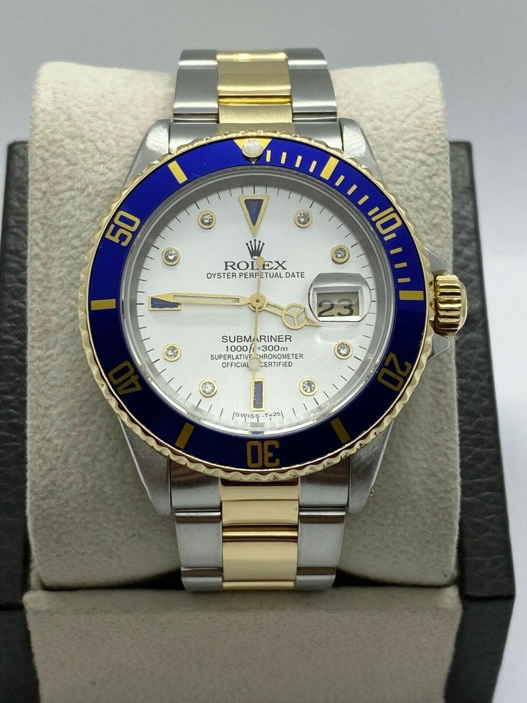 Style Number: 16613  Serial: S316***  Model: Submariner  Case Material: Stainless Steel  Band: 18K Yellow Gold & Stainless Steel   Bezel:  18K Yellow Gold  Dial: Custom Serti Blue Sapphire and Diamond Dial   Face: Sapphire Crystal   Case Size: