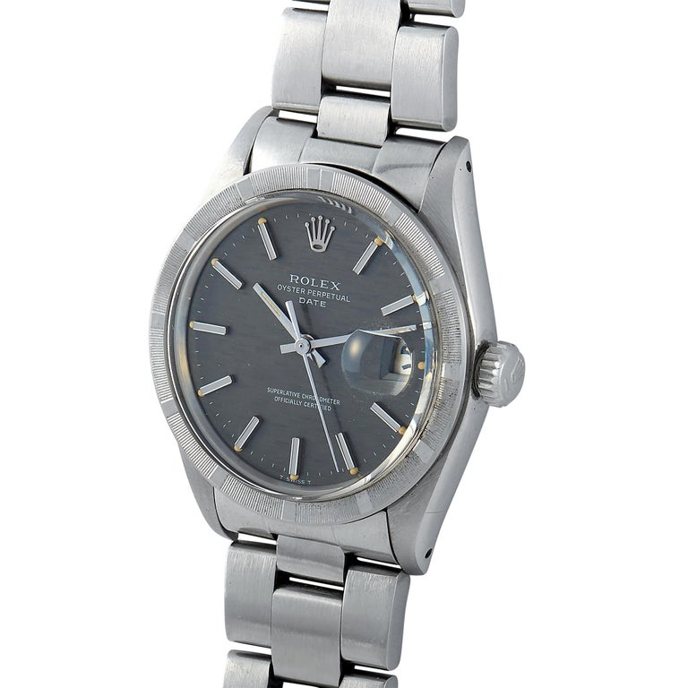 The vintage Rolex Oyster Perpetual Date watch, reference number 1501, boasts a waterproof stainless steel case that is fitted with an engine turned stainless steel bezel. The case measures 34 mm in diameter and is presented on a stainless steel