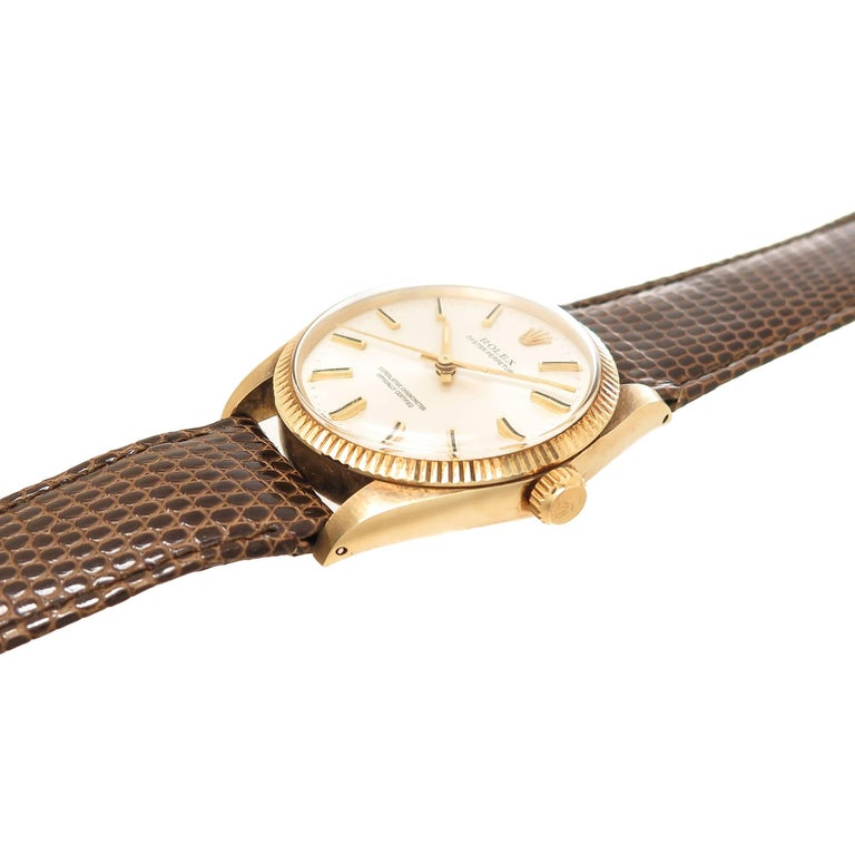 Circa 1974 Rolex Oyster Perpetual Wrist Watch, 34 M.M. 14K Yellow Gold Oyster Case with Fluted Bezel. 26 Jewel Automatic, Self winding Movement, Silver dial with raised Gold markers and a sweep seconds hand. Brown Lizard Strap with Gold Plate Rolex
