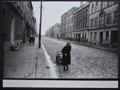 Elder woman walking down the street with her handcart, 1940s till 1950s.