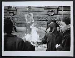 Hungary uprising in back a fire with a poster of Istvan Dobi, 1956.