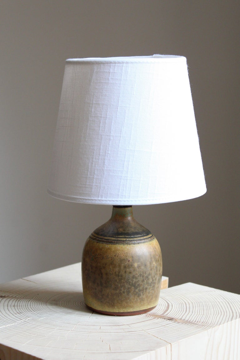 A small table lamp. Produced and designed by Rolf Palm, Sweden, dated 1962.  In glazed stoneware. Brand new high-end lampshade.