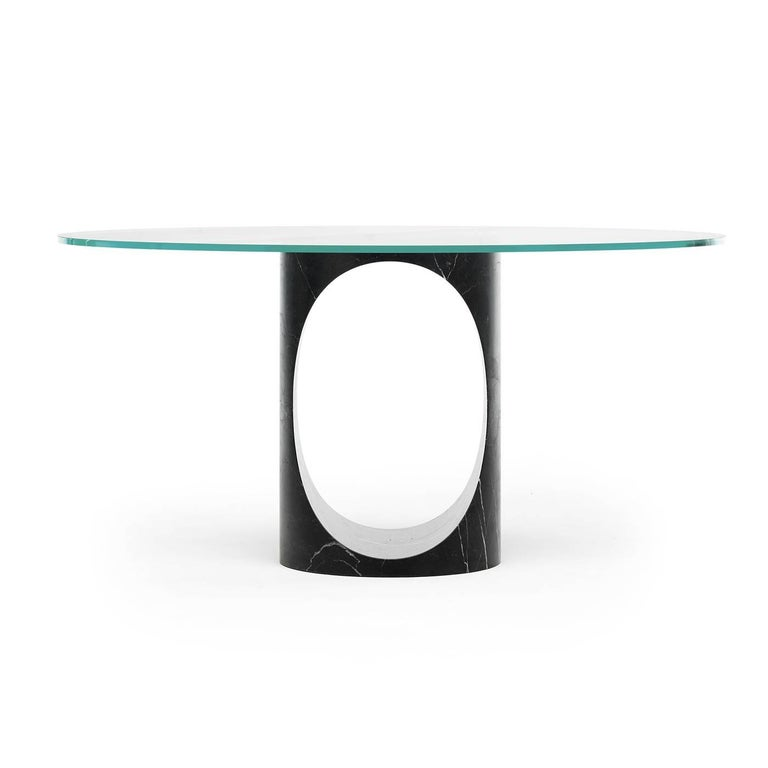 This superb dining table is modern and sophisticated, with a refined combination of contemporary design and noble materials. The base is carved from a single block of New Saint Laurent marble and boasts a dynamic silhouette enhanced by the striking