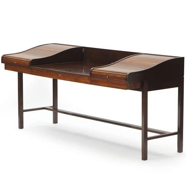 A stately and elegant rosewood and mahogany campaign desk having three drawers and two rosewood roll-top compartments flanking a central writing surface with a flip-down back splash, floating on a spare, architectural rectilinear base.