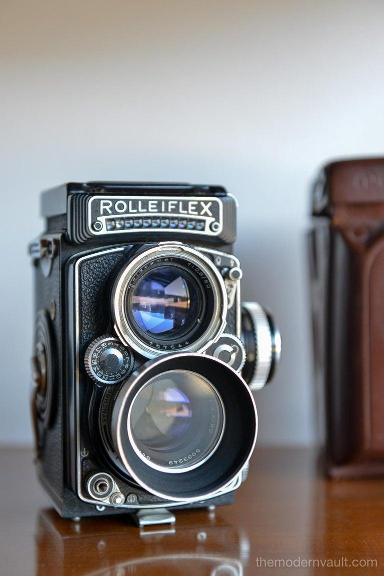 Rolleiflex 2.8E TLR Medium Format Camera with case and accessories, circa 1958. Schneider-Kreuznach Xenotar 2.8 Lens Includes original pistol grip shutter release, Ikophot Light Meter, lens cap, lens hood, original manuals and Rolleigrafie magazine