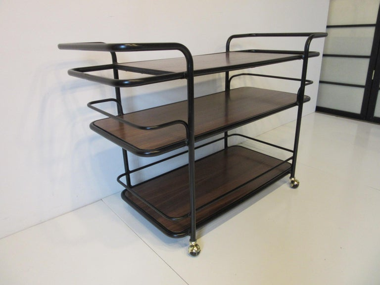 A satin black painted metal rolling bar cart with walnut shelves, brass wheels and each end having storage areas for bottles and glasses. In the manner of Art Deco and the International Style using the tubes and curves of that periods design