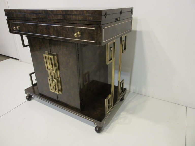 A well-crafted high quality dark Carpathian burl wood rolling bar cart with a top that folds out on both sides having laminate to the inside surface to protect it from wetness and extending the length. Brass details in the wood, center drawer and