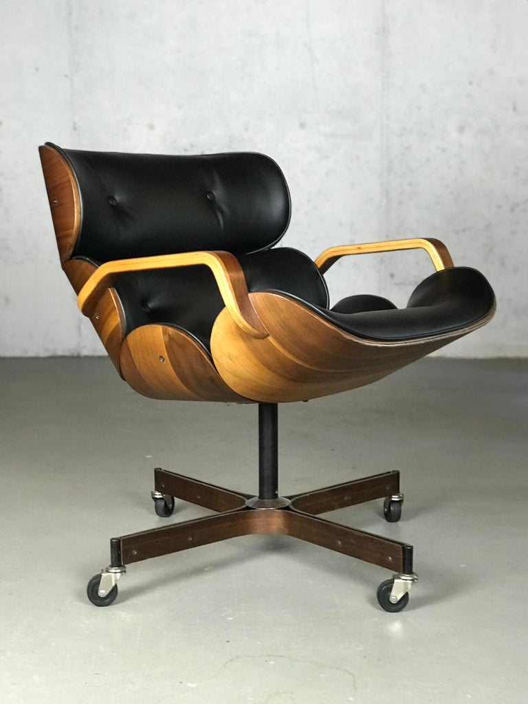 Walnut encased scarce segmented back lounge or desk chair on castors by George Mulhauser for Plycraft. Refinished wood shells and reupholstered in black vinyl. Legs have slight wear. Does not tilt 29.5