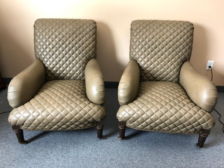 Sumptuous pair of taupe quilted leather club chairs and ottomans having gorgeous workmanship, nailhead detailing, and mahogany turned feet on casters. The ottomans curve to fit into the chairs to allow them to be used like chaises.  Measures: Chair