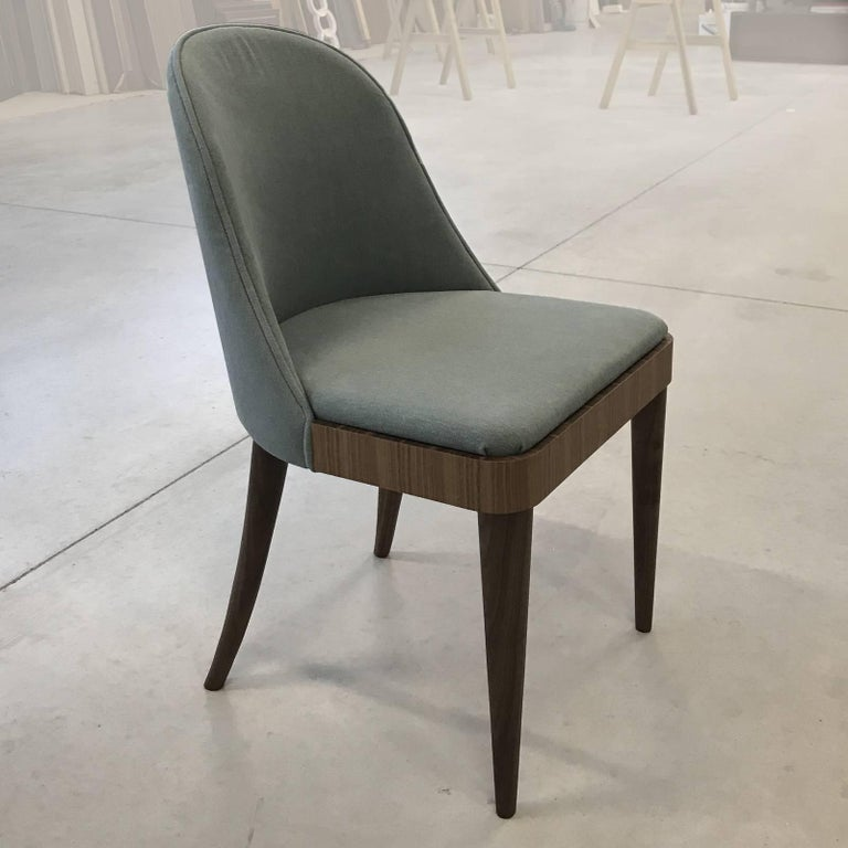 This elegant chair with its midcentury allure, is entirely made in solid Canaletto walnut wood. The finish of the wood can be natural or grey and the cushions can be upholstered in leather or fabric.