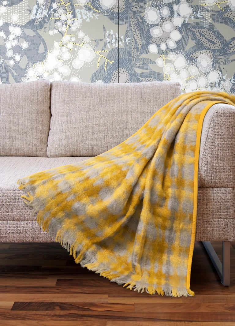 Elegantly soft, the Roma mohair plaid gives the final touch to any environment. This warm plaid, in shades of grey with a hint of gold, is edged in yellow suede on both sides without fringes, echoing the color of the check. The natural softness of