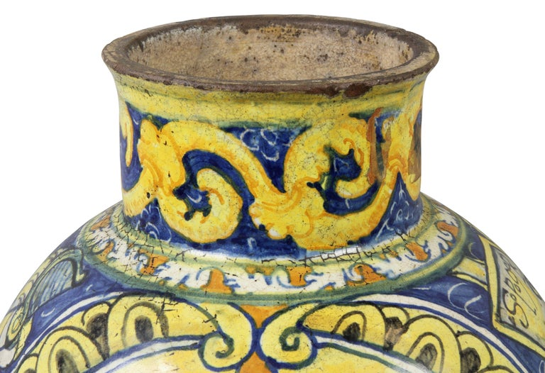 Globular shape decorated with yellows and blues with central cherub and a variety of other decoration. Signed on side of body. SPQR.