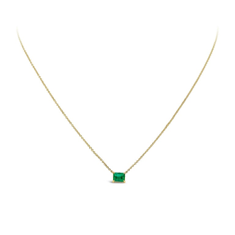 A classic solitaire pendant showcasing a 1.04 carat emerald cut green emerald, set in a four-pong basket made in yellow gold. Suspended on a 16 inch yellow gold chain (length of chain can be changed upon request).   Style available in different