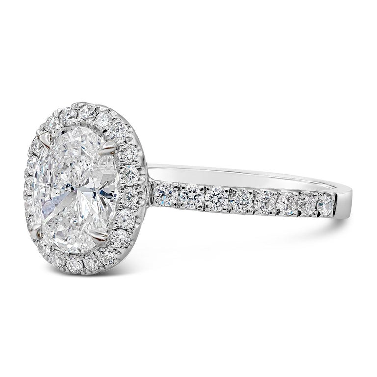 A timeless engagement ring style showcasing a 1.05 carat oval cut diamond surrounded by a single row of round brilliant diamonds. Set in an accented diamond band made in 18k white gold. Accent diamonds weigh 0.44 carats total. Center diamond is D