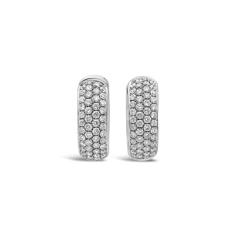 A stylish pair of huggie hoop earrings showcasing round brilliant diamonds weighing 1.19 carats total, micro-pave set in a domed setting made in 18k white gold. Diamonds are approximately F color, VS-SI1 clarity.  Style available in different price