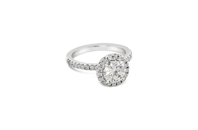 A timeless piece showcasing a 1.22 carat round brilliant diamond, surrounded by a single row of round diamonds in an accented 18k white gold mounting. Accent diamonds weigh 0.43 carats total.   Style available in different price ranges. Prices are