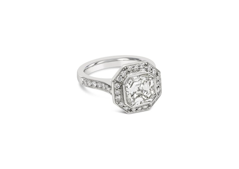 A unique engagement ring style showcasing a 2.07 carat asscher cut diamond, bezel set in a brilliant diamond halo. Set in a polished platinum band accented with more round diamonds. Accent diamonds weigh 0.40 carats total. Size 5.25  Style available
