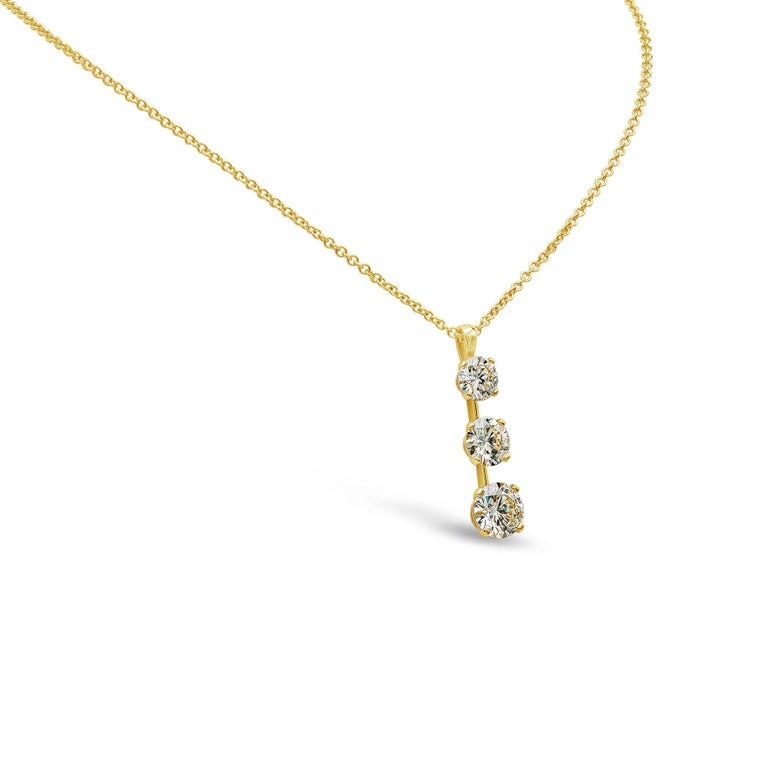 A beautiful drop necklace style showcasing three round brilliant diamonds graduating in size, set in a polished 18k yellow gold mounting. Diamonds weigh 7.05 carats total (1.74ct, 2.12ct, 3.19ct).   The piece is certified by IGI, M-N color VS-SI