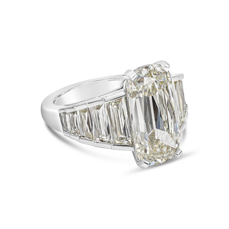 A unique and desirable diamond engagement ring showcasing an elongated cushion cut diamond weighing 5.60 carats total. The center diamond is flanked by perfectly-matched and custom cut trapezoid french cut diamonds (1.77 carats total) set in a