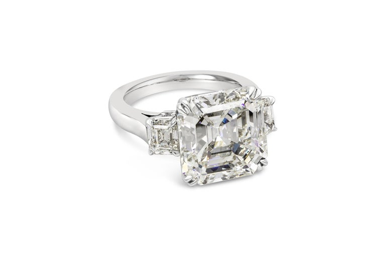 A subtle and sophisticated three stone engagement ring featuring a 9.20 carat asscher cut diamond certified by GIA as J color, VS2 clarity. Flanking the center diamond are 1.15 carats total of emerald cut diamonds set in a polished platinum