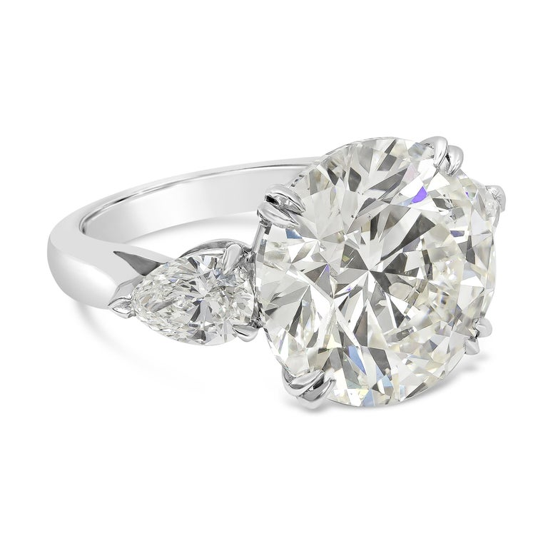 Showcasing a 10.09 carat Round Diamond certified by GIA as K color, SI2 clarity, flanked by pear shape diamonds weighing 1.22 carats total. Made in platinum.   Style available in different price ranges. Prices are based on your selection of the 4C's