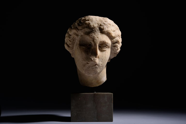Roman marble head of Athena, circa 1st-2nd century AD.  Her head turned slightly to the left, the lips once parted, the almond-shaped eyes framed by a sweeping brow and her hair swept backwards, in long, thick, wavy curls, covering the tops of the