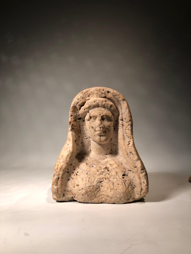 Travertine veiled female bust. Levante, Roman period, 2nd-3rd century AD. One can clearly observe the imprints of the sculptor's tools left on the stone. Nice small scale sculpture of the large life size ones seen at temples and cemeteries.