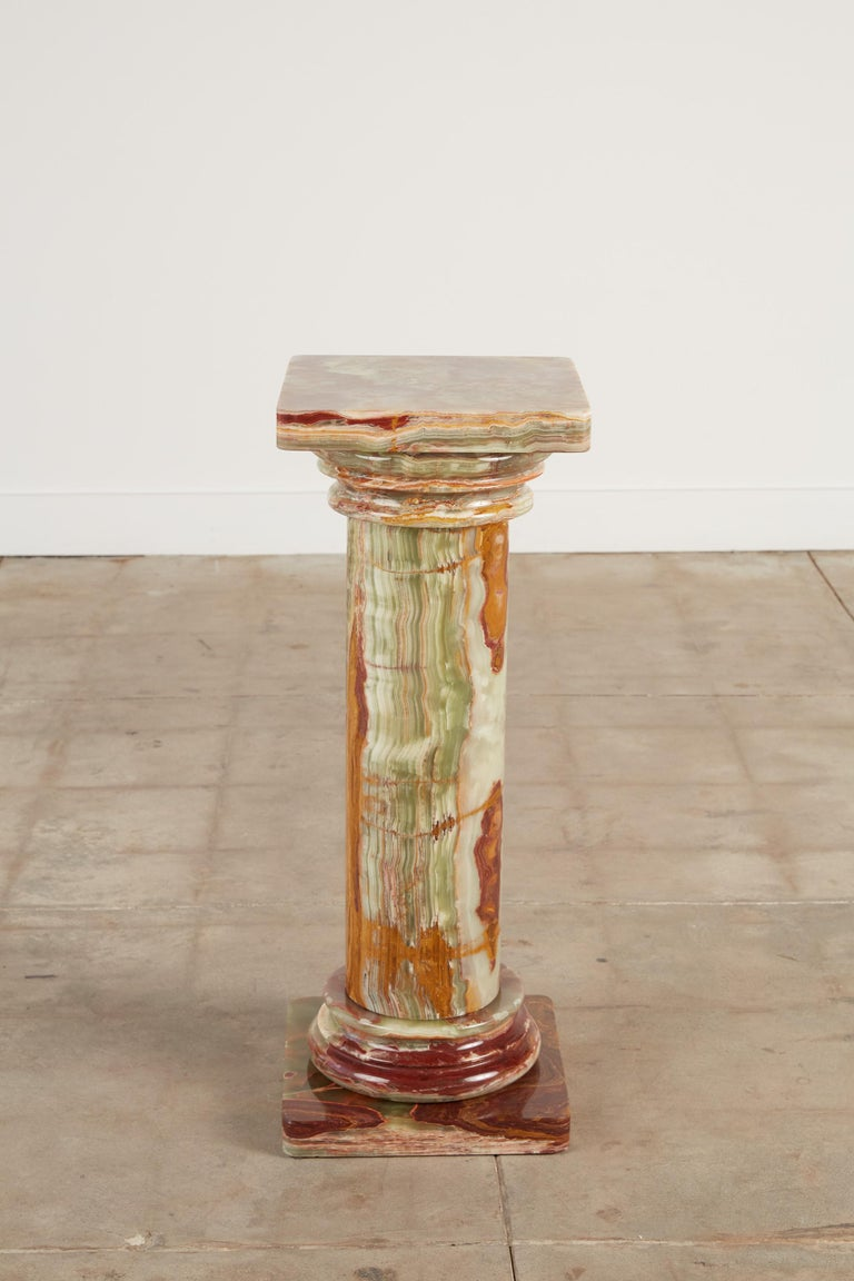 Roman style onyx pedestal. The pedestal features a multicolored hand carved onyx body in the style of Roman column with Tuscan style capital details on the top of and bottom of the piece. The pedestal is constructed of five separate pieces of onyx