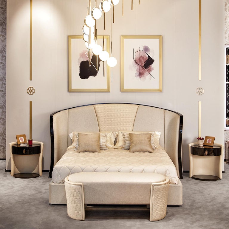 Channeling major middle to late-twentieth century vibes, the Romantic bed features an upholstered headboard with quilted leather detailing. The headboard envelops the top of the bed with curving panels, creating a cozy feel. A complementary
