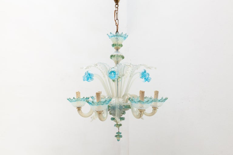 Venetian Murano glass chandelier featuring a design of intricate blue glass flowers and milk glass leaves. Lit by 6 bulbs.  Dimensions: W.55 diameter x 60 H cm :Chain length: 35 H cm.