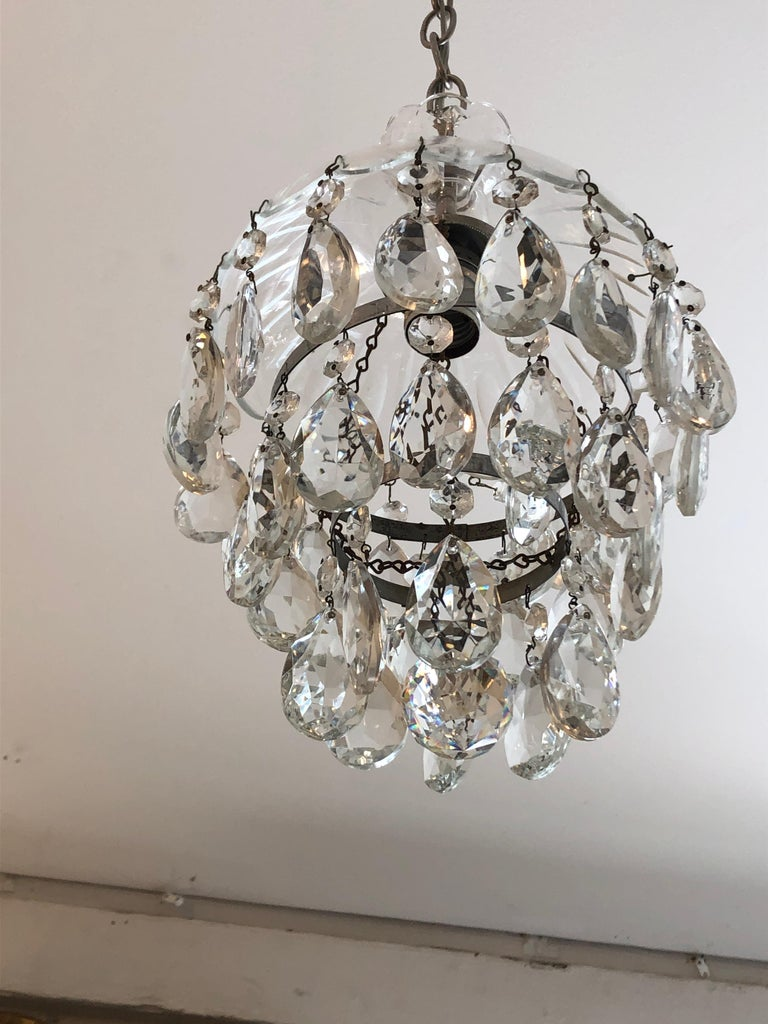 A very pretty small sized pair of glamorous pendant chandeliers having cut glass dome shaped tops and 3 levels of dripping tear drop crystals and a round crystal ball at the bottom.
