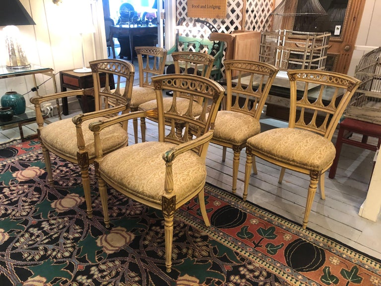 A romantic vintage set of 6 Italianate style carved wood painted and gilded dining chairs including two armchairs and 4 sides, having beautiful aged patina and neutral color of yellowish cream and gilt with some undercoat of green showing through