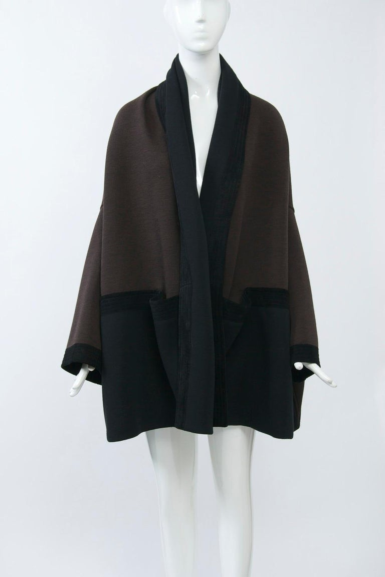 Romeo Gigli designs are highly sought after. This jacket, composed of black and brown wool knit trimmed in black suede, has an oversized kimono silhouette. The black suede borders are channel-stitched and, where they horizontally separate the brown