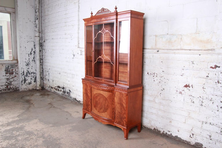 A gorgeous inlaid flame mahogany breakfront china display cabinet or bookcase