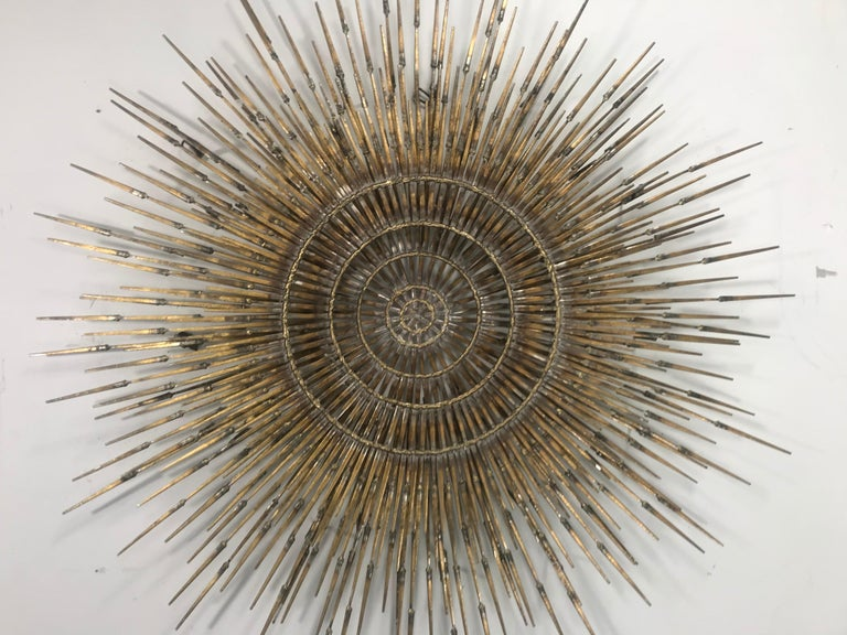 A large 4 layer Brutalist sunburst with starburst overlay nail art wall sculpture by Ron Schmidt.  Very uncommon multiplanar design with brass welded iron nail rays radiating sunburst-style from a central brass ring that floats in front of an open