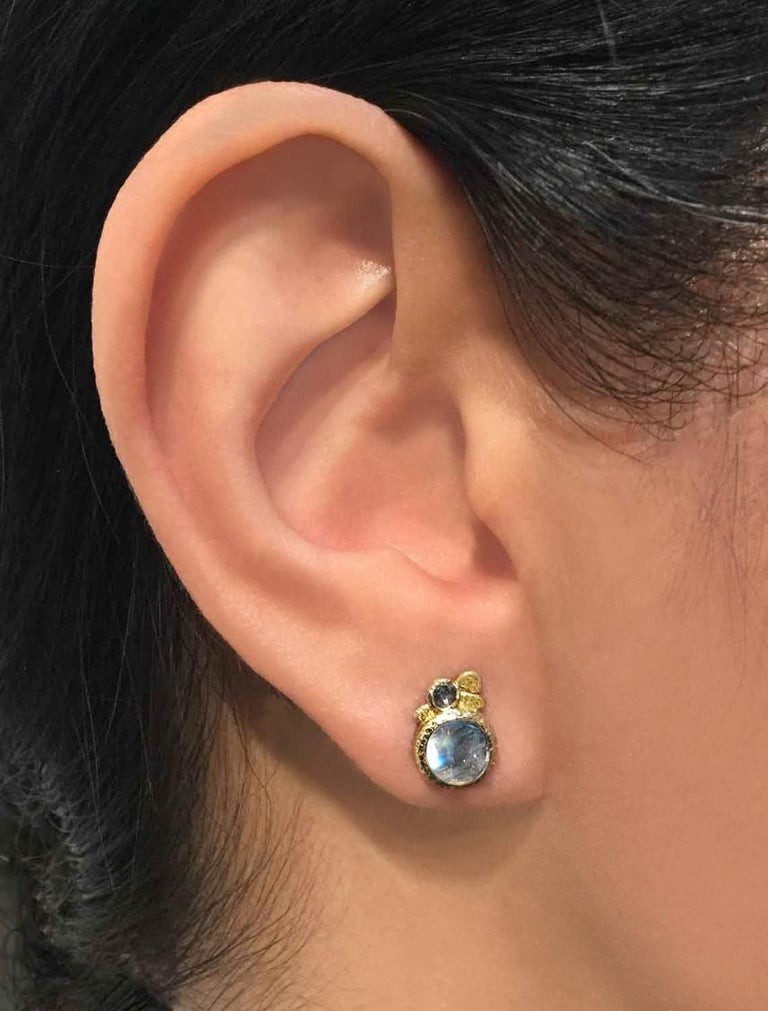 One of a Kind Earrings handcrafted by jewelry maker Rona Fisher featuring a matched pair of glowing blue moonstone, bezel-set in beautifully-textured 18k yellow gold and accented by a pair of round rose-cut salt and pepper diamonds. Stamped and