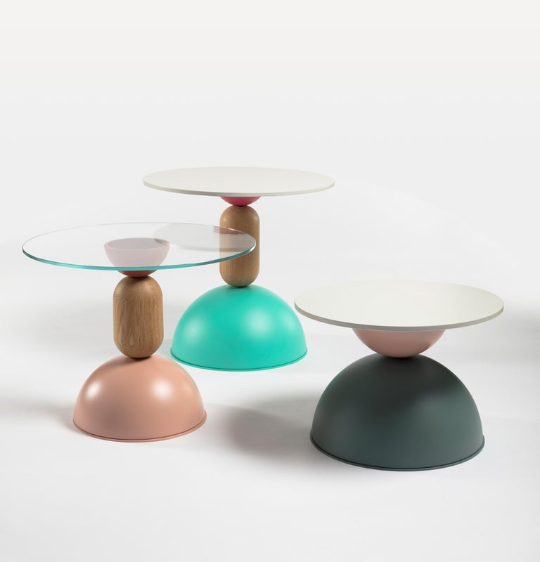 A collection of small tables of different sizes and heights, composed of a versatile superimposition of curved shapes made of wood and coloured metal. Like dancing figures, these furnishings - at the same time playful and functional -