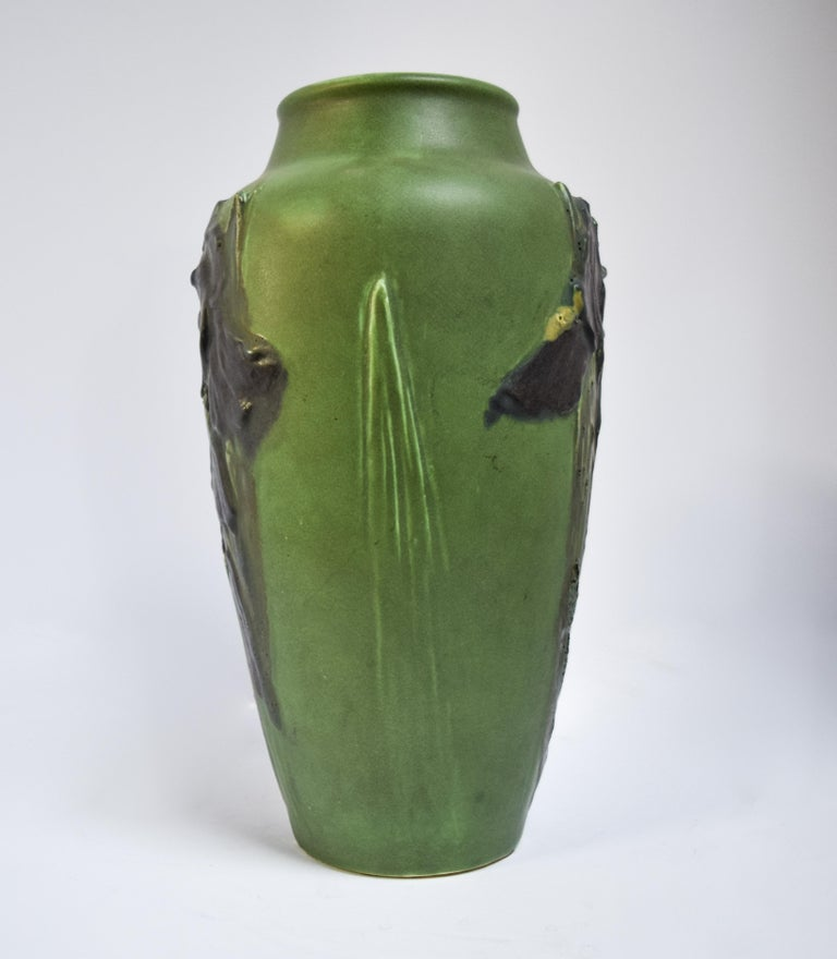 A staple of American pottery, the work of Albert Pons was a major influence on the Rookwood Pottery Company at the turn of the century during the Arts & Crafts movement. Crafted in 1905, this vase is a fabulous green adorned with purple iris' in