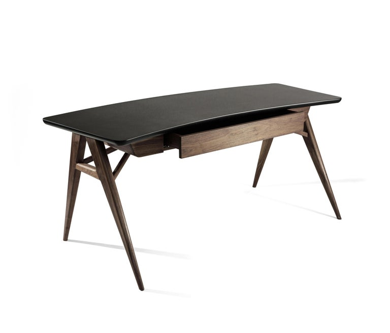 The Roos desk made of walnut mahogany and steel has a classic triangular, suspension configuration in with an elegant curved lacquered top for a smooth finish.