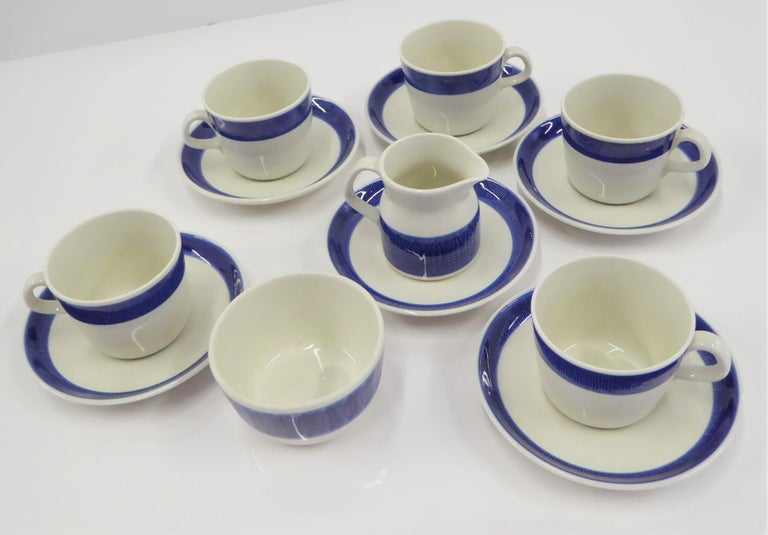 A Rörstrand coffee / tea set of cups, saucers, creamer and sugar bowl in the KOKA BLÅ pattern designed by Hertha Bengtson, was first manufactured in 1956 and remained in production until 1988. The translation of the name is Boil/ Scald Blue which